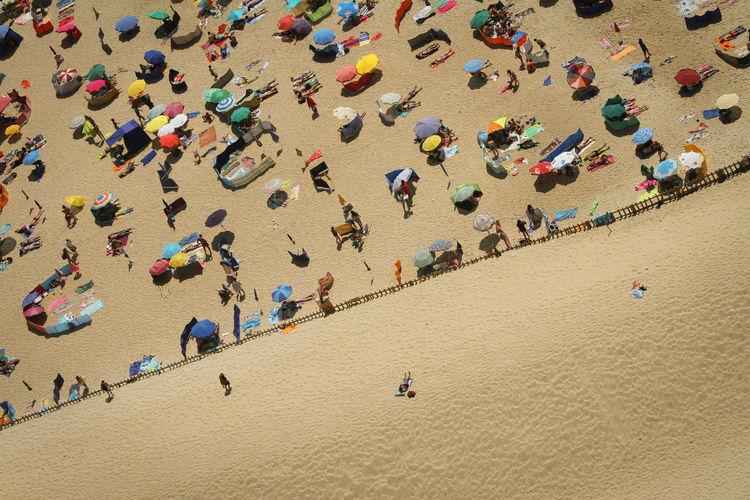 Aerial View Of Tourist Resting Under Beach Umbrellas