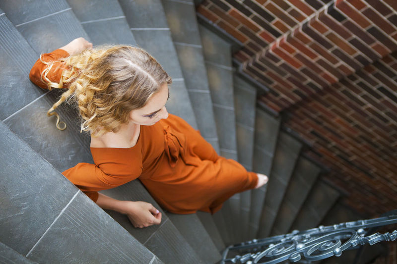 High angle view of girl sitting on staircase