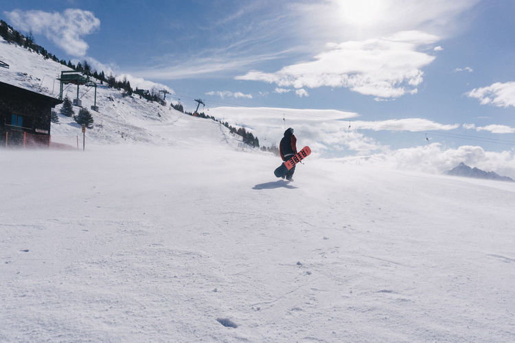 Man riding motorcycle on snowy field against sky