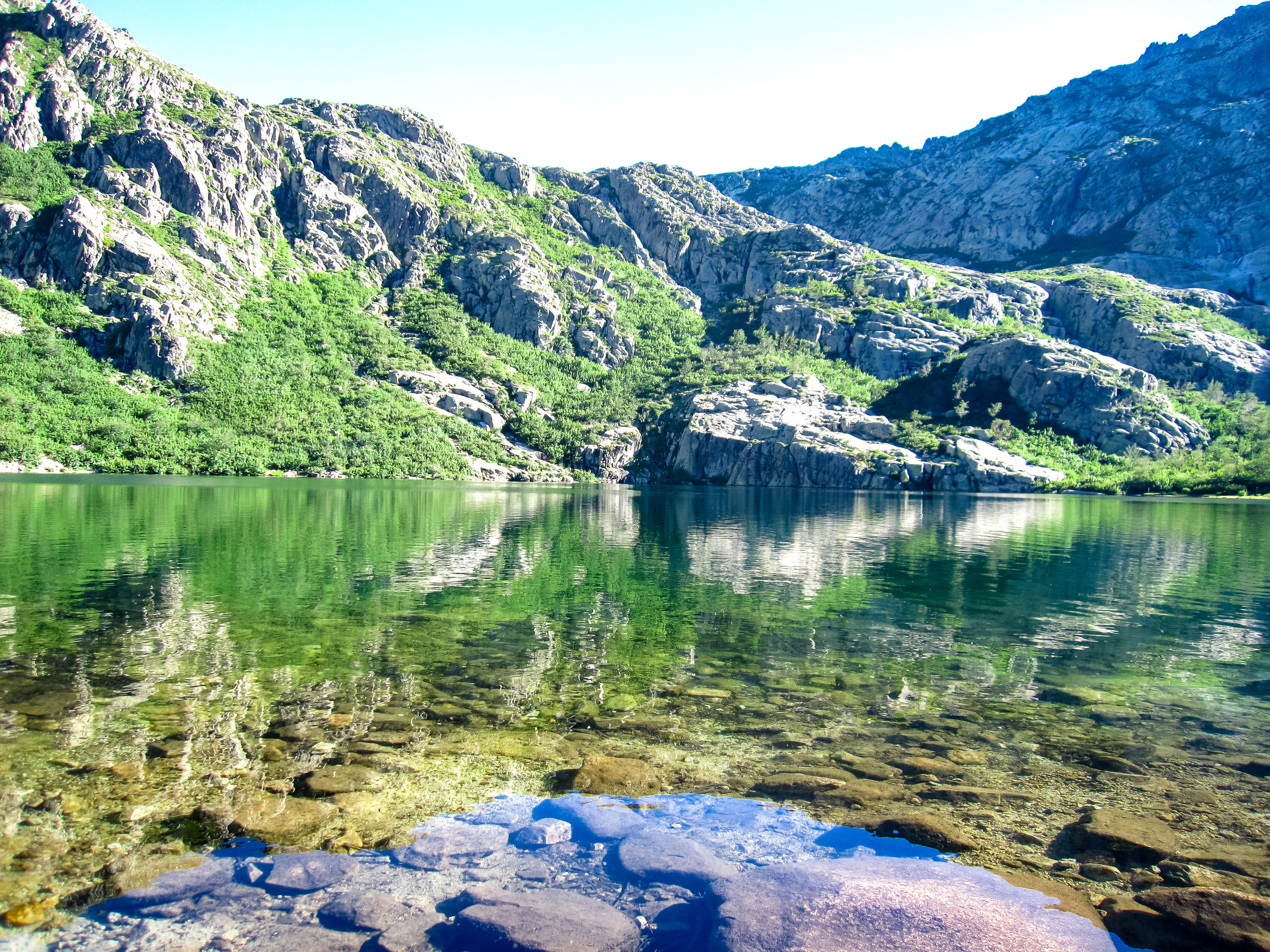 water, lake, beauty in nature, scenics - nature, tranquility, tranquil scene, mountain, reflection, nature, rock, day, no people, sky, idyllic, non-urban scene, solid, plant, rock - object, outdoors, formation