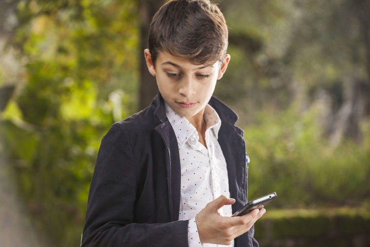 Thoughtful teenage boy holding mobile phone