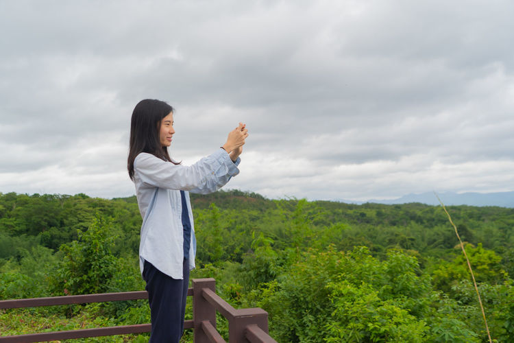 Side view of woman photographing while standing on observation point against sky