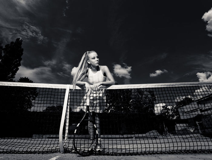 Woman holding tennis racket while standing by tennis net against sky