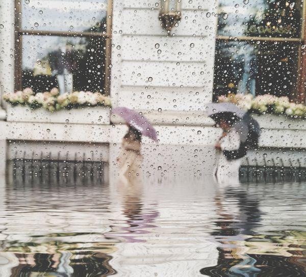 Two People Walking In Flooded City Street In Rain