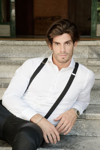 Portrait man wearing suspenders while sitting on steps
