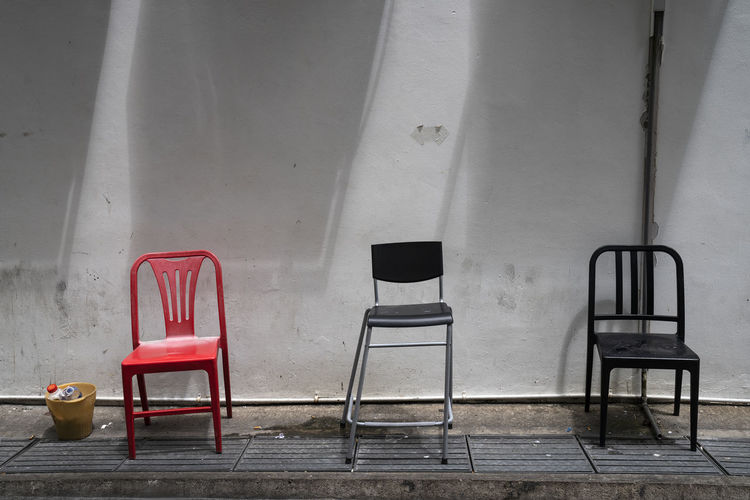 Empty chairs and table against wall in building