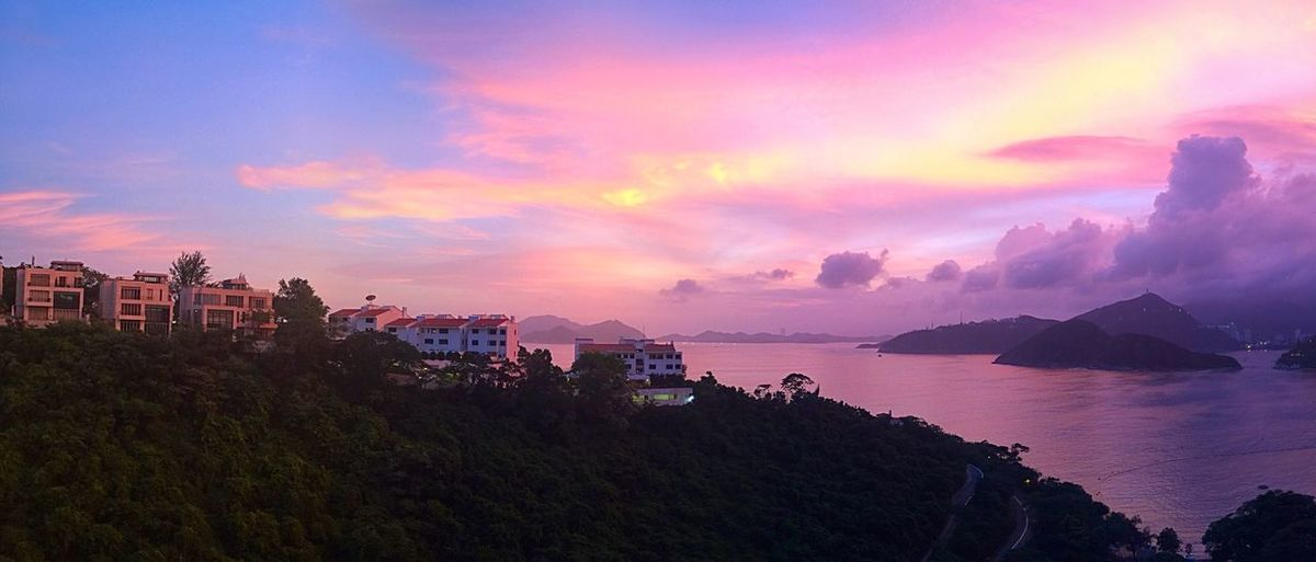 Panoramic shot of buildings on island against sky during sunset