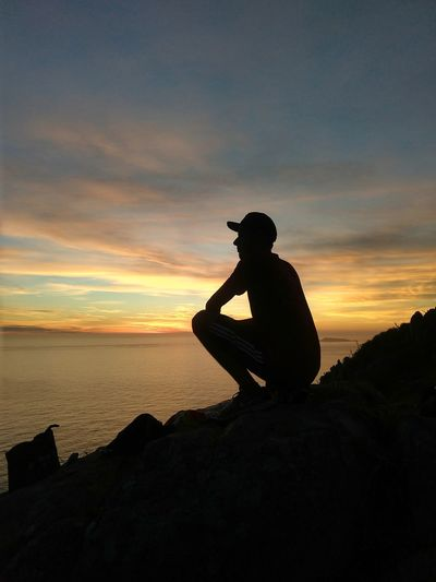 Silhouette man sitting on rock against sea during sunset