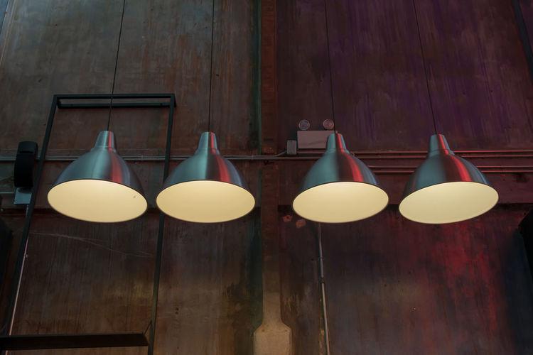 Close-up of illuminated light bulb hanging on wall