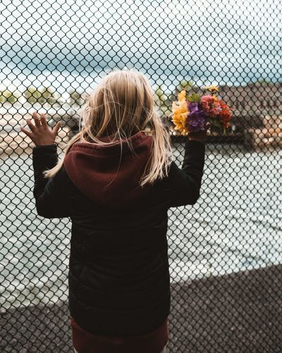Rear view of woman standing by chainlink fence