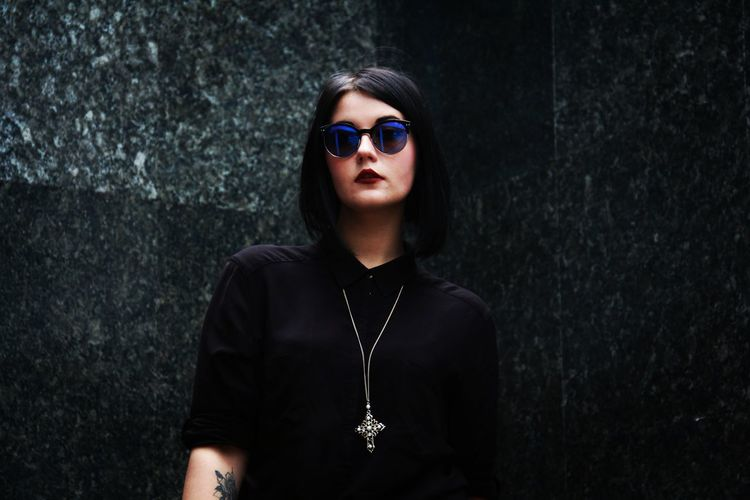 Portrait of goth young woman wearing sunglasses