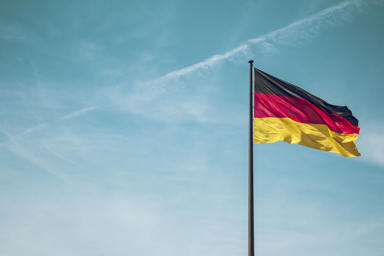 Low Angle View Of German Flag Against Blue Sky