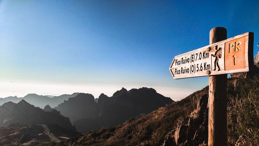 Information sign by mountains against clear sky