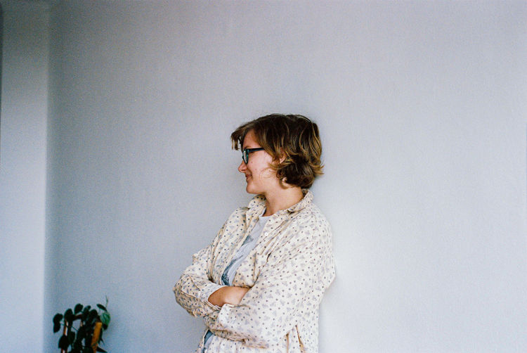 Woman looking away against wall
