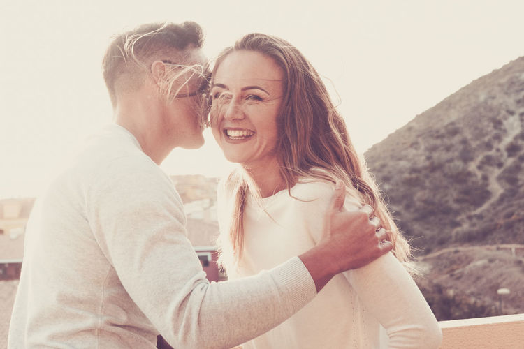 Smiling Couple Embracing While Standing In Balcony
