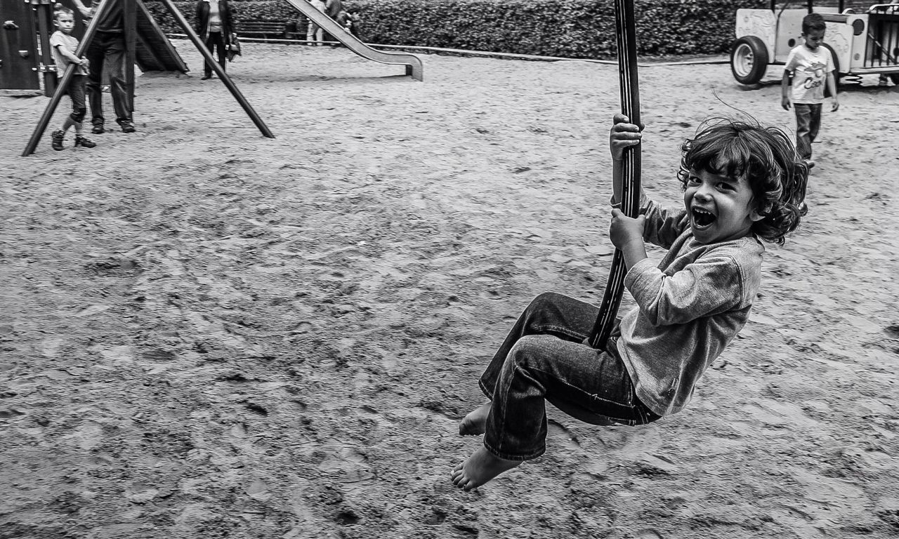 Portrait of happy girl swinging in playground