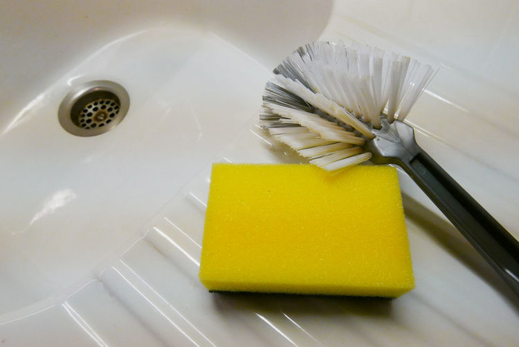 Close-Up Of Brush And Sponge Scrub In Sink