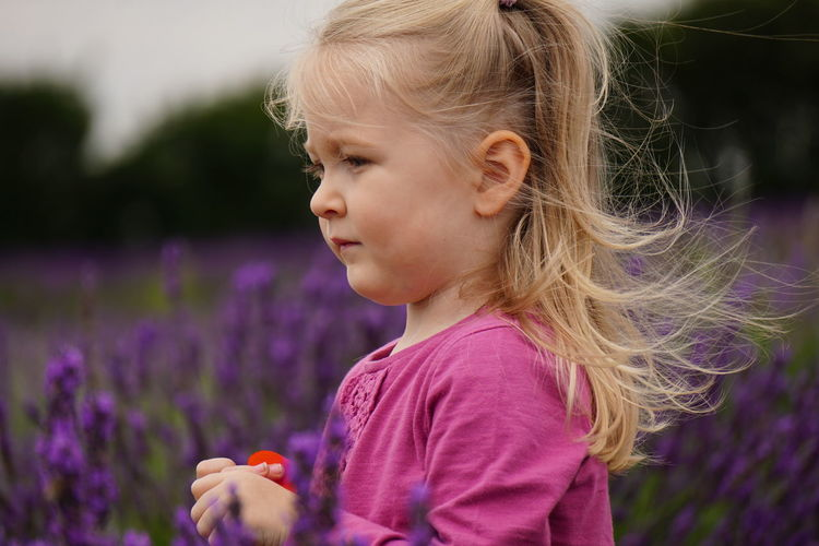 Close-up of girl amidst flowers on field