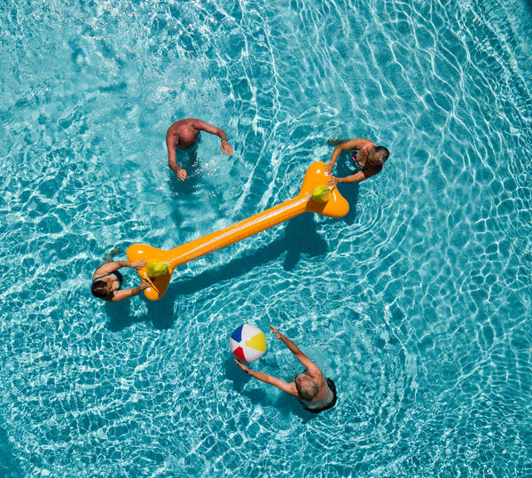 High angle view of people floating in swimming pool