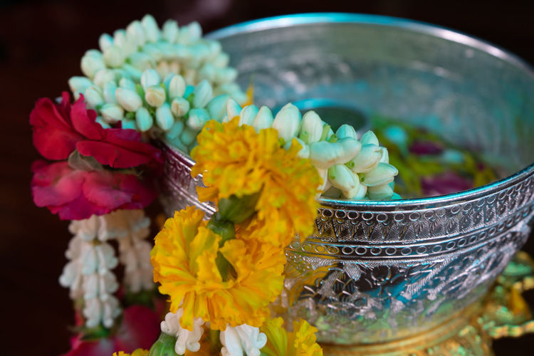 Closeup flower garlands hanging on the edge of silver bowl with flower petal floating on the water in background Flower Flowering Plant Plant Vulnerability  Freshness Fragility Nature Beauty In Nature Petal No People Selective Focus Flower Head Blooming Garland Jasmine Roses Marigold Craftsamanship Handmade Cultures Religion Thailand Festival Decoration Closeup Blurred Motion Forest Backgrounds