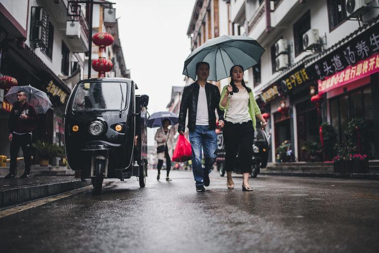 People walking on wet street in rainy season