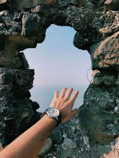 Cropped hand of person by hole in stone wall