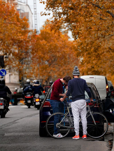 Rear view of people walking on street during autumn