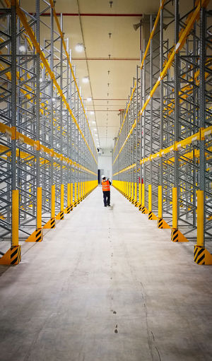 The Way Forward Architecture Direction One Person Built Structure Real People Transportation Rear View Men Diminishing Perspective Full Length Lifestyles Building Bridge Day Indoors  Yellow Walking Ceiling Warehouse Distribution Warehouse Worker