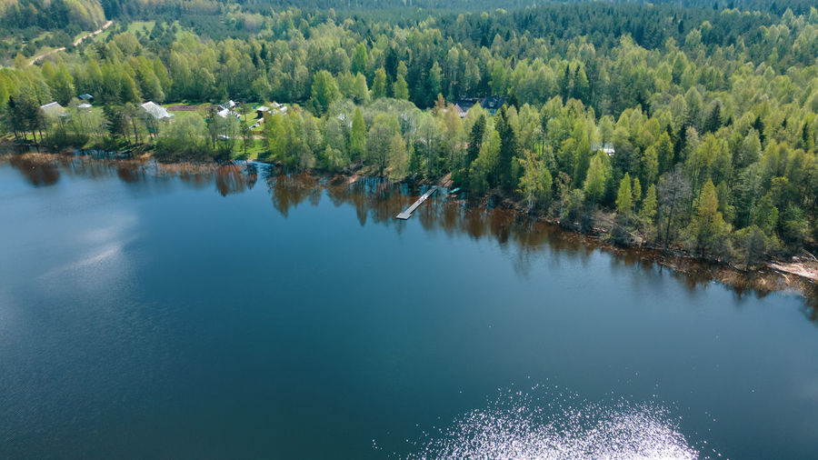 A beautiful scenery, a lake, a forest, a small village from a bird's eye view. ideal for fishing.