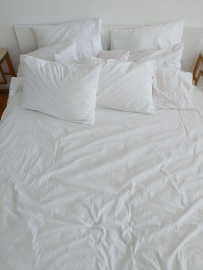 Hotel bed with white pillows and sheets