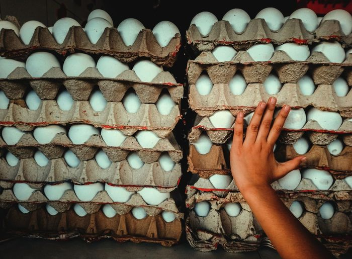 Cropped hand touching stack of egg cartons