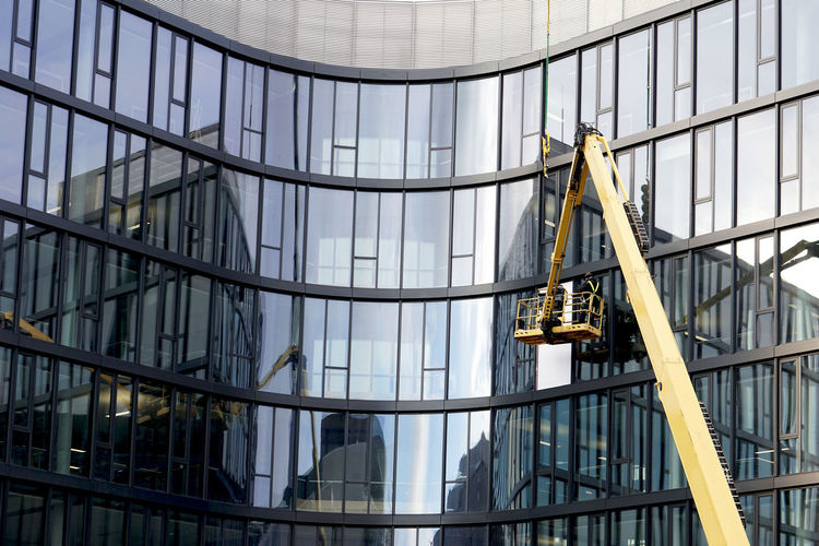men at work Built Structure Architecture Glass - Material Building Exterior Modern Day Low Angle View Building Office Building Exterior Office City Reflection Outdoors Occupation Full Frame Transparent Shape Window Industry Crane Man At Work Men At Work  Modern Architecture Reflections