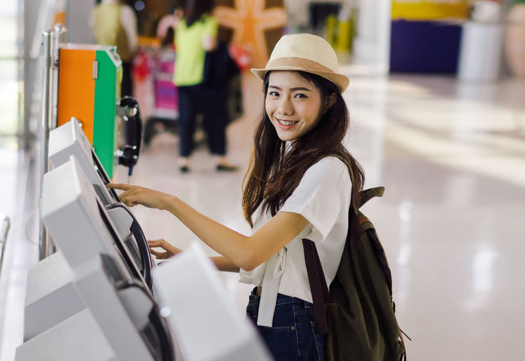 Portrait Of Smiling Young Woman Making A Reservation At Airport