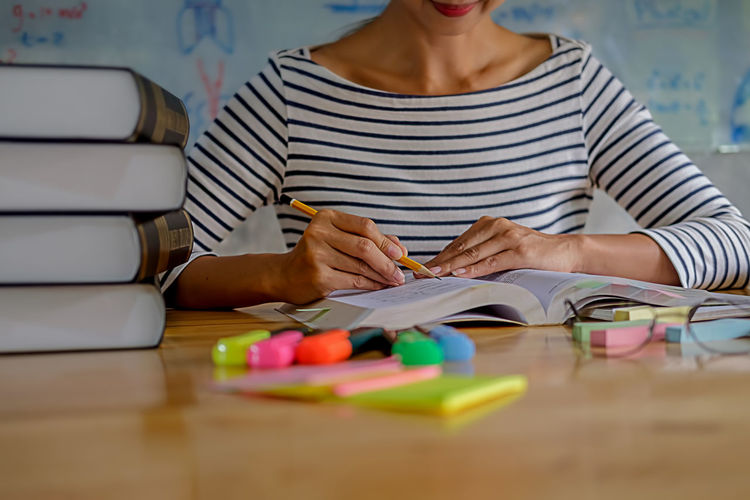 Woman studying with school supplies on table at home