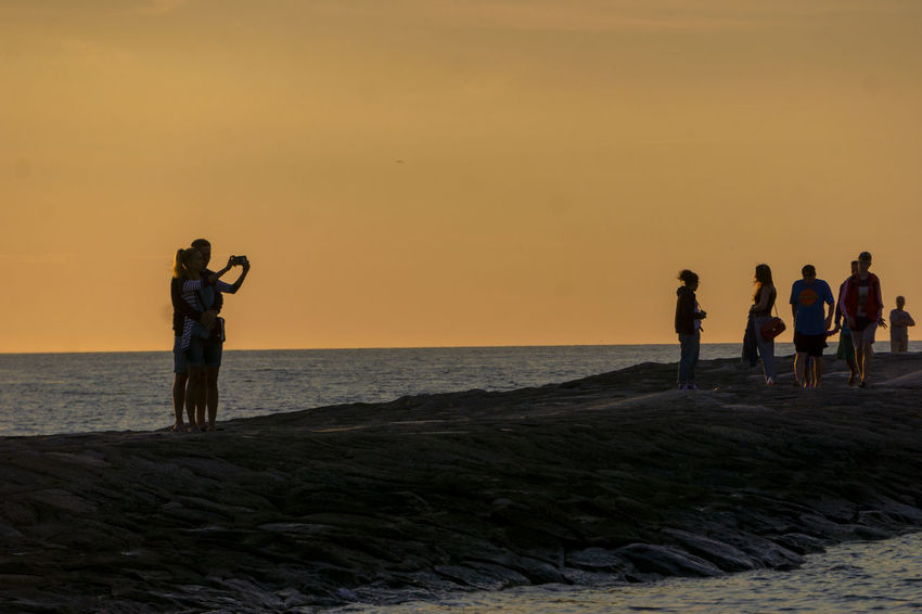 Beach Beauty In Nature Group Of People Horizon Horizon Over Water Land Leisure Activity Lifestyles Men Orange Color Outdoors Real People Scenics - Nature Sea Selfie Sky Standing Sunset Togetherness Water Women The Traveler - 2018 EyeEm Awards