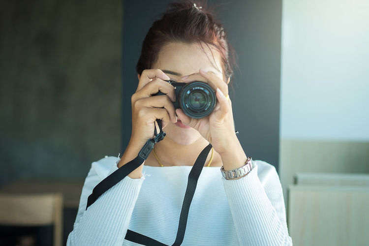 Close-up of young woman photographing with camera
