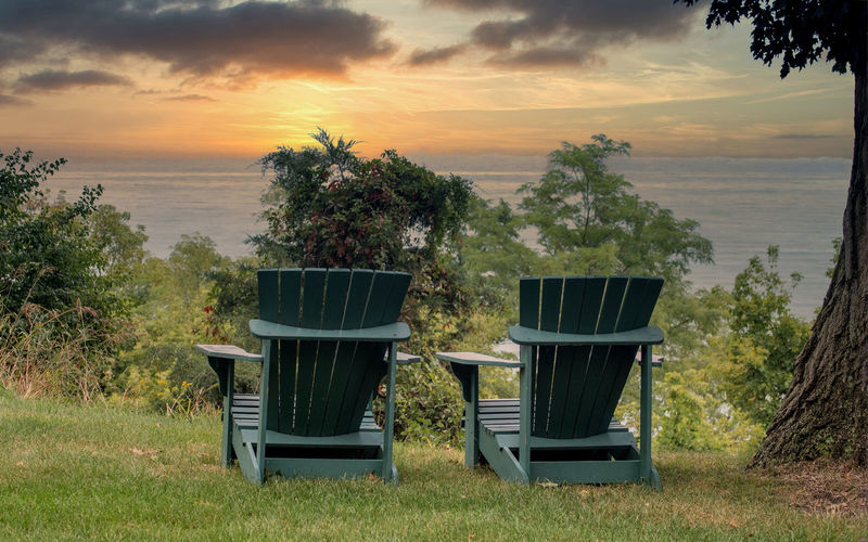Empty chairs by trees against sky during sunset
