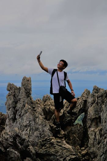Smiling young man taking selfie on rock formations