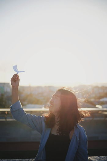 Woman flying paper airplane against sky