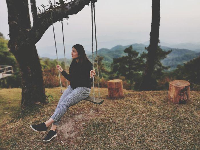Full length of woman on swing against trees