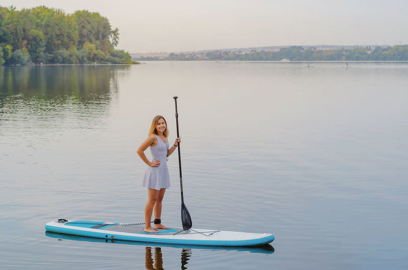 Young woman in a dress swims on the lake on surfboard
