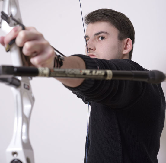 Man Aiming With Bow And Arrow Against White Background