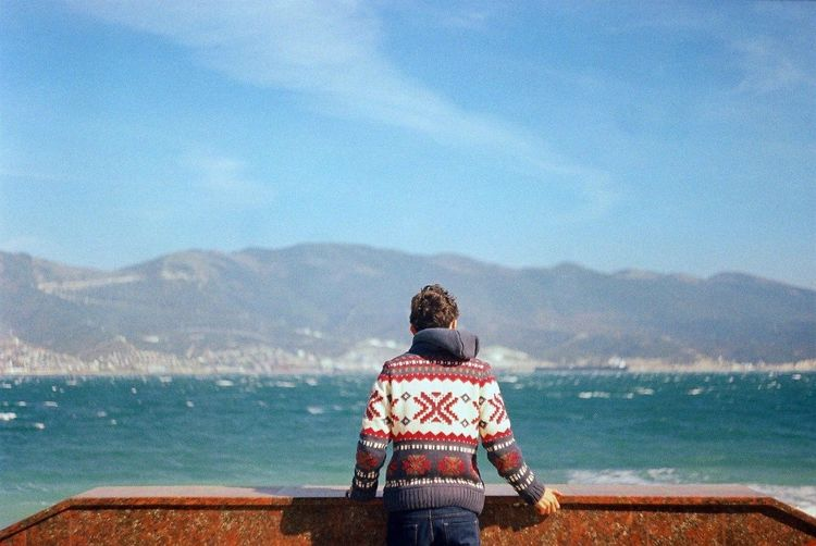 Rear view of man standing by sea against sky