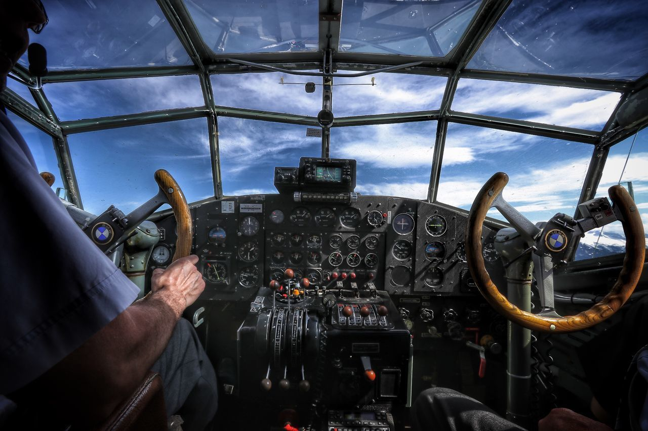 airplane, mode of transportation, air vehicle, transportation, cockpit, human hand, hand, pilot, control, men, vehicle interior, glass - material, real people, human body part, control panel, flying, travel, sky, one person, piloting, uniform, aerospace industry, co-pilot, finger