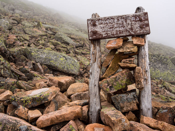 Weathered trail sign along there Cathedral Trail on Katahdin, in Baxter State Park, Maine. Sign Trail Sign Trail Footpath Hiking Katahdin Baxter State Park Maine Mountain Wood - Material Weathered Nature Rock No People Day Rock - Object Landscape Outdoors Stone Extreme Terrain Foggy Wooden Wooden Post Adventure Barren