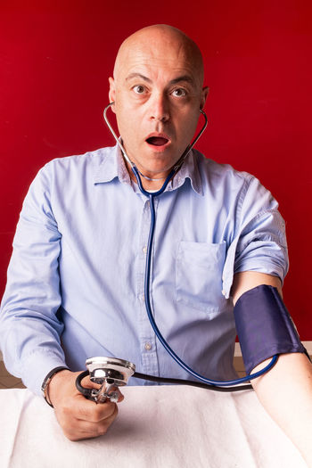 Portrait of shocked man checking blood pressure at table against red wall