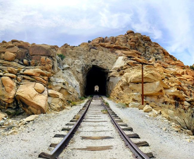 Railroad tracks amidst rock formation against sky