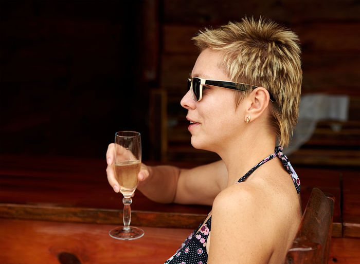 Side view of woman holding champagne while sitting at restaurant