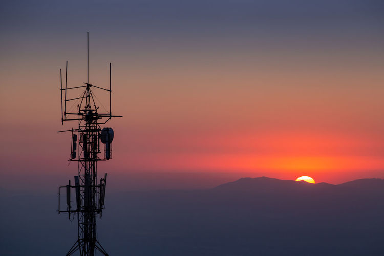 Silhouette of communications tower against orange sky