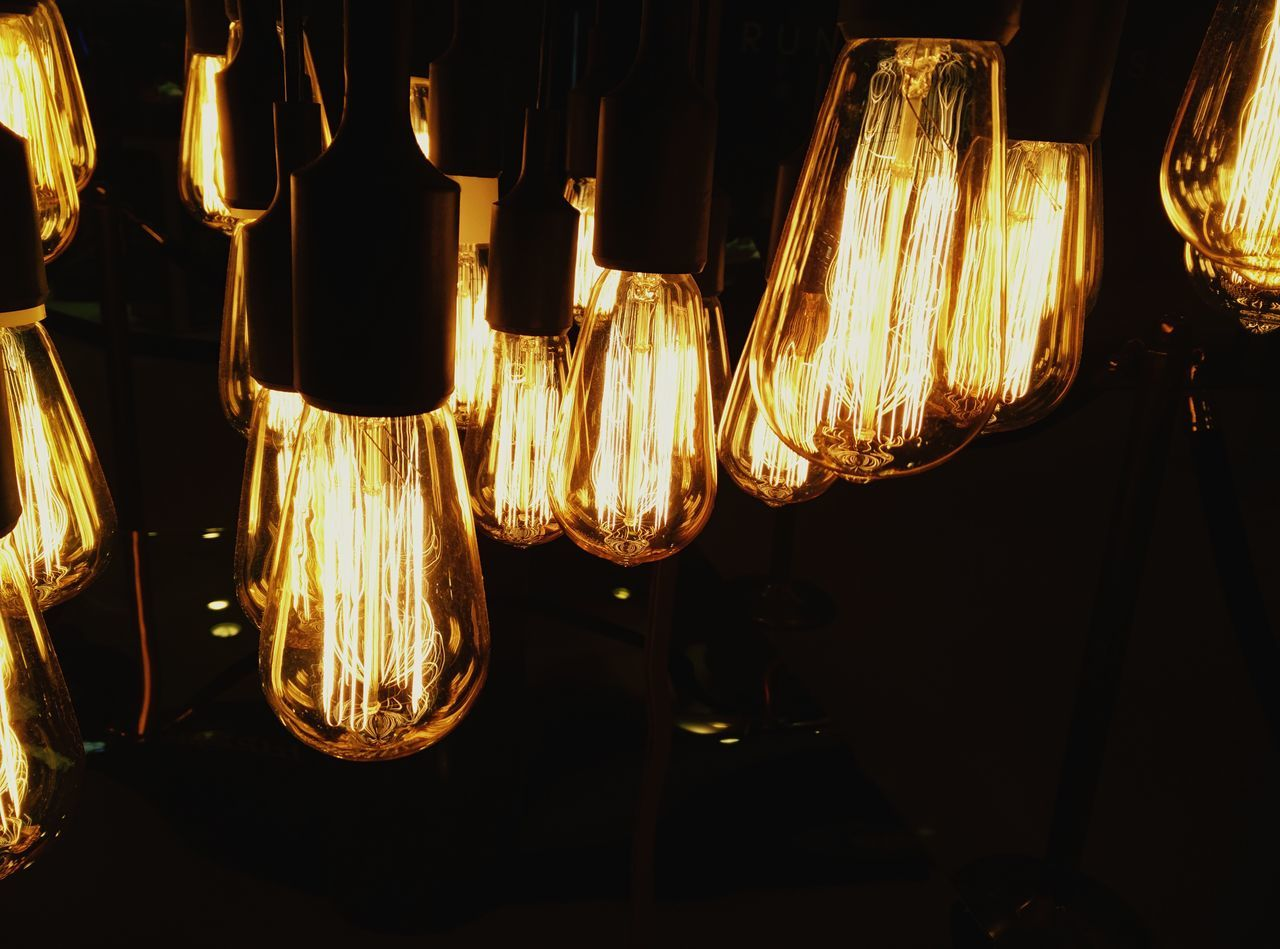Low Angle View Of Illuminated Light Bulb Hanging At Night